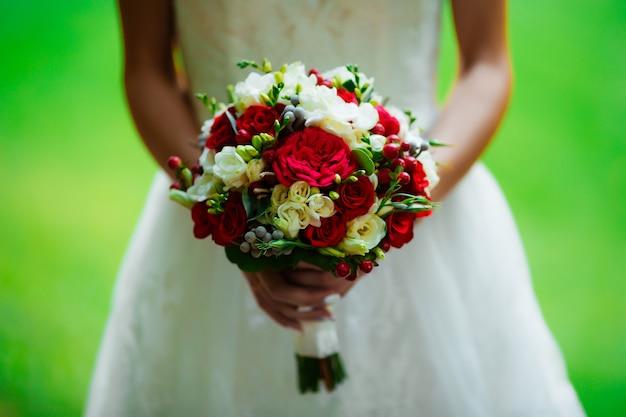 Bruid in een trouwjurk en een boeket bij zonsondergang in het park