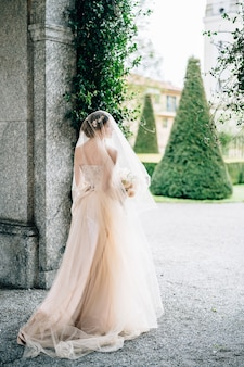Bruid in een trouwjurk met sluier en een boeket bloemen staat bij de boog