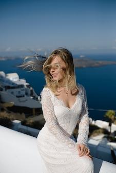 Bruid in een trouwjurk op het strand door de zee tegen de achtergrond van een blauwe hemel.
