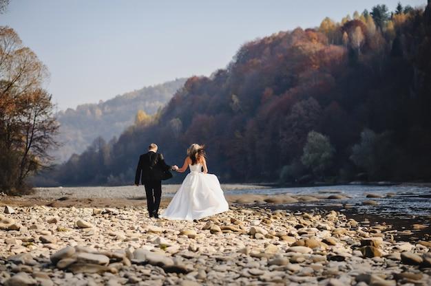 Bruid in een witte jurk en bruidegom gaan naar de rivier rotsen en hand in hand