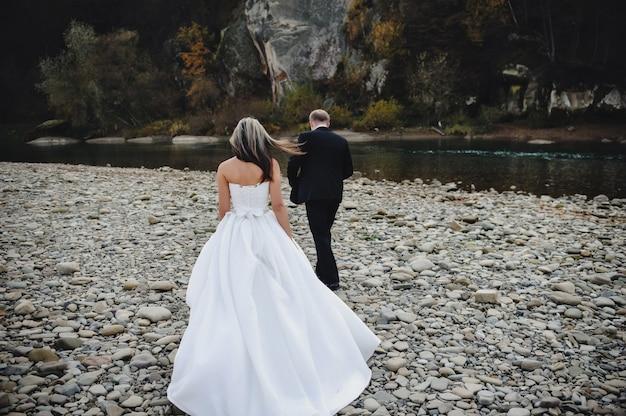 Bruid in een witte jurk en bruidegom gaan naar de rivier stenen