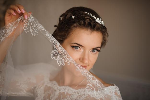 Bruid in een witte jurk en een zachte make-up houdt de sluier in de hand