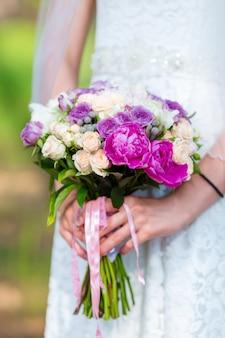 Bruid in een witte jurk in zomer groen park met bruiloft boeket in handen