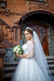 Bruid in een witte jurk met een boeket in haar handen en een kroon op haar hoofd