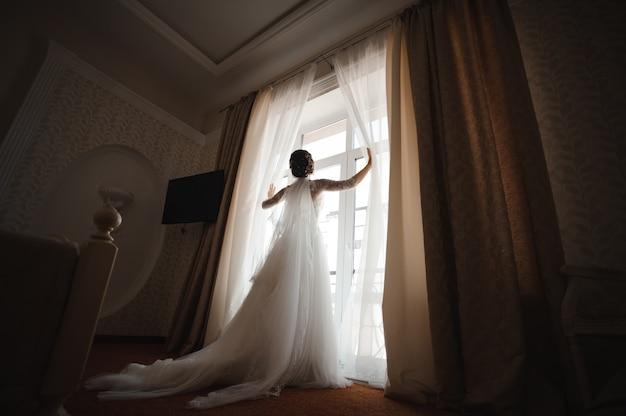 Bruid in een witte jurk met een pluim opent de gordijnen