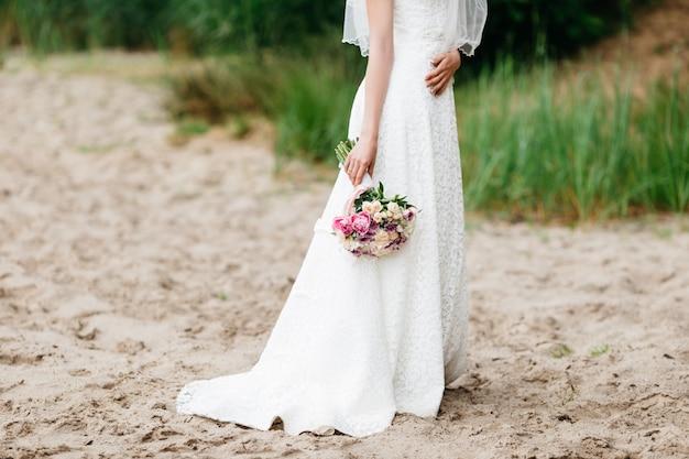 Bruid in een witte jurk op het strand van de zomer met bruiloft boeket in handen