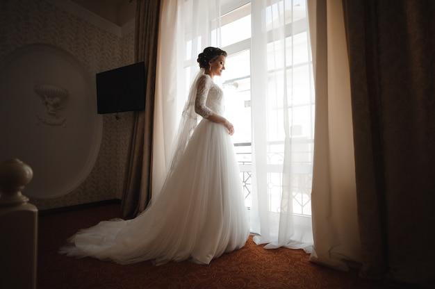 Bruid in een witte kanten jurk met een pluim staat tegen het raam