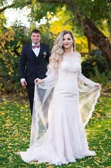 Bruid in jurk en bruidegom in de tuin