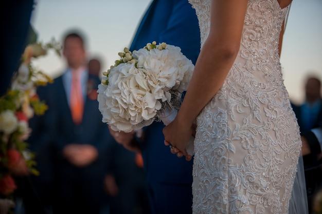 Bruid in jurkje met kristallen staat met boeket in haar handen