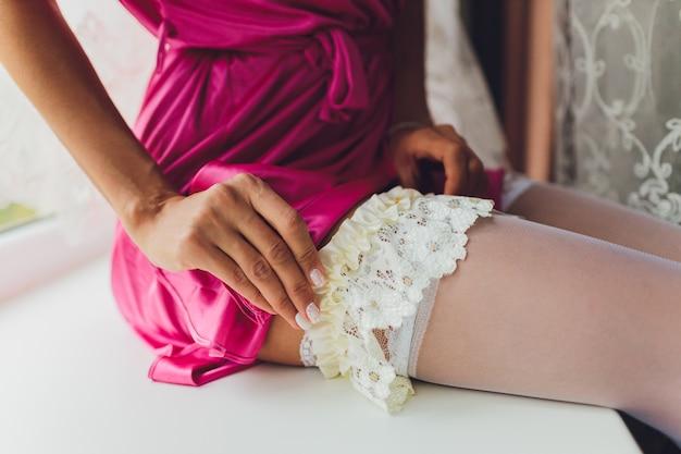 Bruid in kousen en een kousenband op haar been