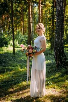 Bruid in lange witte jurk staat in park tussen bomen met boeket bloemen, zomer bruiloft