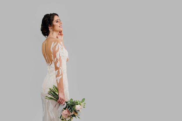 Bruid in luxe trouwjurk met boeket in studio op witte lege muur rechts. advertentie voor sociale netwerken voor huwelijksbureau en bruidssalon.