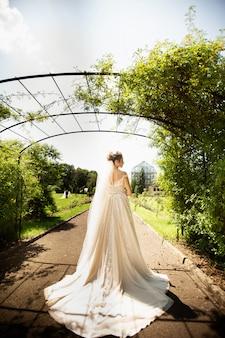 Bruid in mode trouwjurk op natuurlijke achtergrond. een mooi vrouwenportret in het park. achteraanzicht