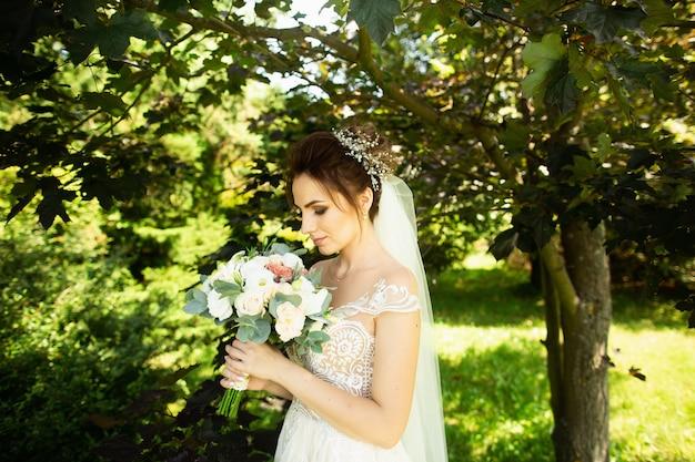 Bruid in mode trouwjurk op natuurlijke achtergrond. een mooi vrouwenportret in het park