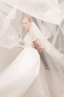 Bruid in mooie jurk permanent binnenshuis in witte studio interieur zoals thuis. trendy bruiloft stijl schot. jong aantrekkelijk kaukasisch model zoals bruid het tedere kijken.