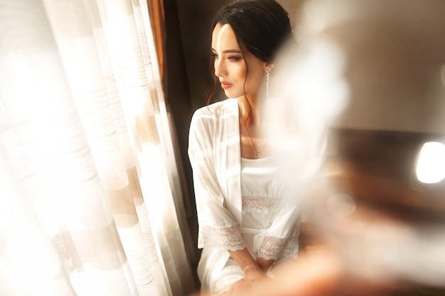 Bruid in mooie kledingszitting op stoel binnen in wit studiobinnenland zoals thuis, het schot van de trendy huwelijksstijl