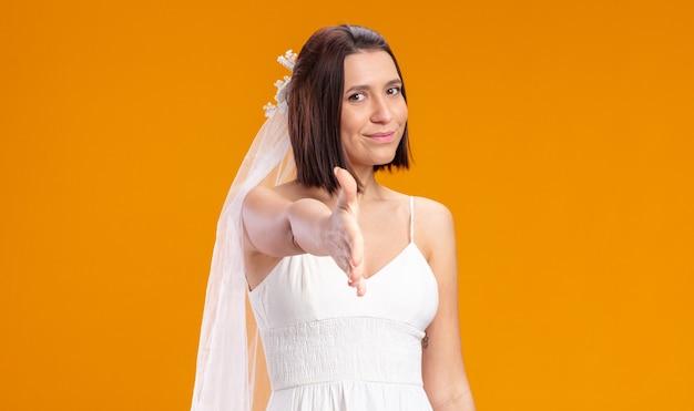 Bruid in mooie trouwjurk die er gelukkig en positief uitziet, zelfverzekerd glimlacht en hand aanbiedt die een groetgebaar maakt