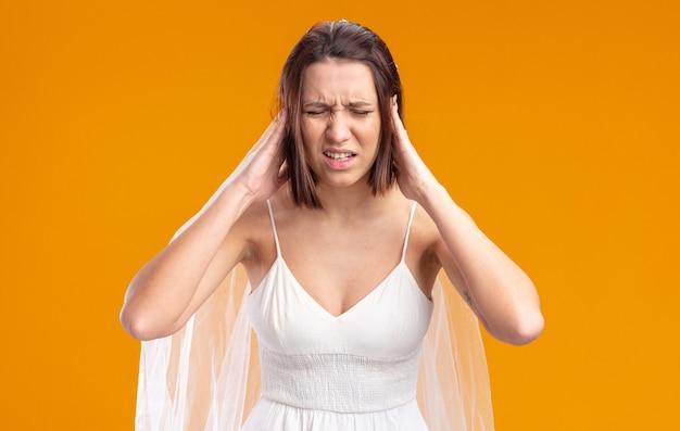 Bruid in mooie trouwjurk die er onwel uitziet en haar hoofd aanraakt met sterke hoofdpijn