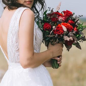 Bruid in trouwjurk en bruiloft boeket te houden