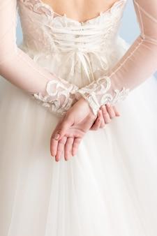 Bruid in trouwjurk houdt handen achter haar rug