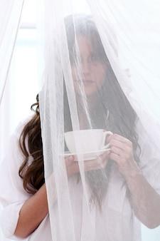 Bruid in trouwjurk met een kopje drinken
