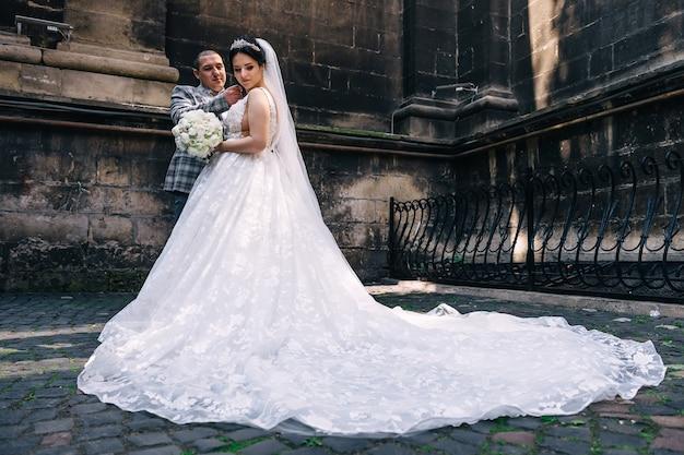 Bruid in trouwjurk met lange staart jurk met een bruiloft boeket. de bruidegom raakt het gezicht van de bruid aan. jonggehuwden bij het bouwen van achtergrond.