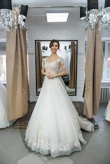 Bruid in trouwjurk poseren met de handen op de taille