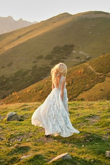 Bruid in vintage bruiloft jurk weglopen zonsondergang spectaculaire berglandschap op de achtergrond