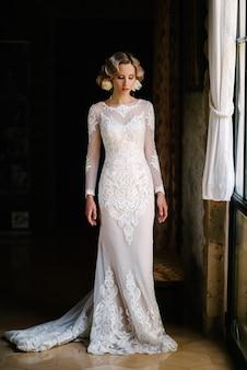 Bruid in witte huwelijkskleding die binnen stellen