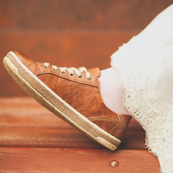 Bruid in witte huwelijkskleding en bruine tennisschoenen of sportenschoenen. dames voet in een sneaker, op een houten geverfde bank, close-up