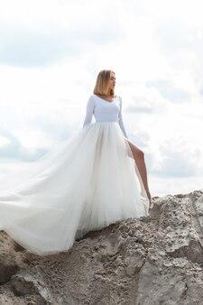 Bruid in witte jurk buiten op het zand en de blauwe hemelachtergrond