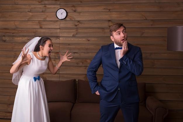 Bruid in witte jurk en sluier die tegen haar bruidegom schreeuwt. jonggehuwden complexe relatie
