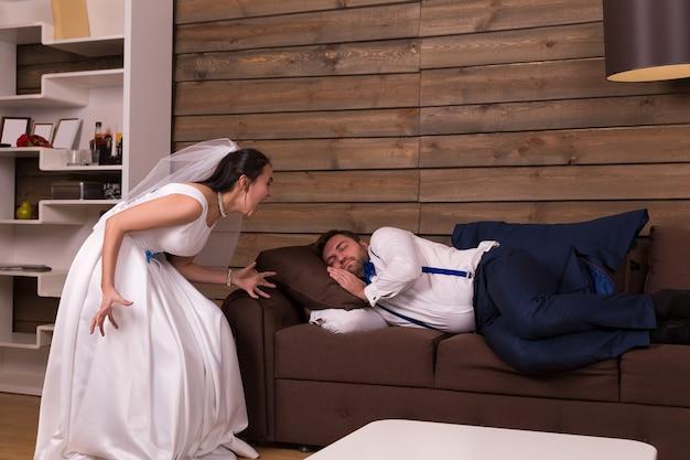 Bruid in witte jurk en sluier schreeuwt op een dronken slaap op de bank bruidegom.