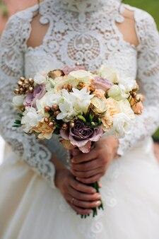 Bruid in witte jurk met een boeket van witte bloemen en groen. witte, paarse, roze rozen.