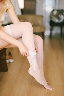 Bruid in witte kousen draagt een kanten kousenband op haar been terwijl ze op een stoel in de kamer zit
