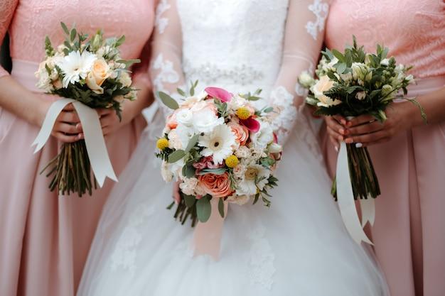 Bruid in witte trouwjurk houdt mooi bruidsboeket met vriendinnen in roze jurken