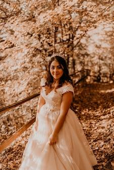 Bruid in witte trouwjurk loopt door de herfst