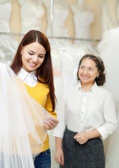 Bruid kiest bruidssluier bij winkel van de bruiloft mode