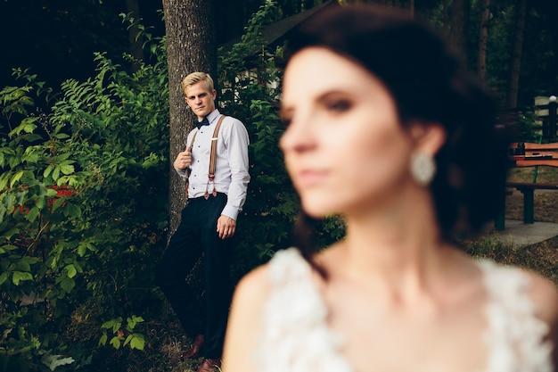 Bruid kijkt ergens op de achtergrond is de bruidegom