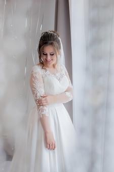 Bruid kijkt uit het raam, trouwdag, ochtend van de bruid