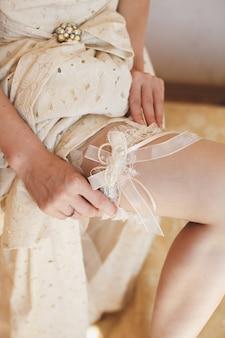 Bruid kleedt jarretel op het been. foto van mooie vrouwelijke blote voeten benen in trouwjurk. bruid kleedt kousen op voeten. bruid die een huwelijkskouseband op haar been zet
