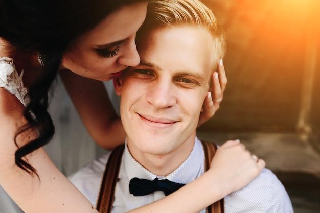 Bruid leunt op de bruidegom en omhelst hem teder