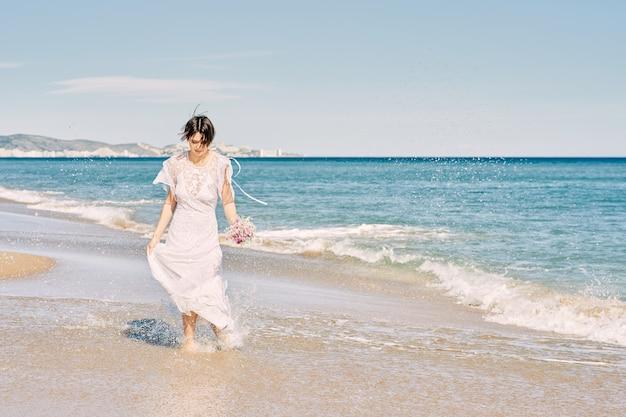 Bruid loopt gelukkig langs het strand in haar trouwjurk en houdt een boeket bloemen in haar hand