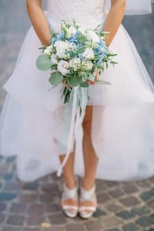 Bruid loopt op de straat met blauw bruiloft boeket