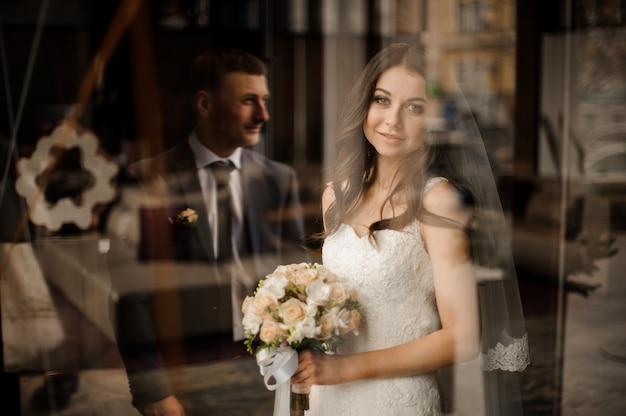 Bruid met boeket van rozen die en op bruidegom glimlachen wachten