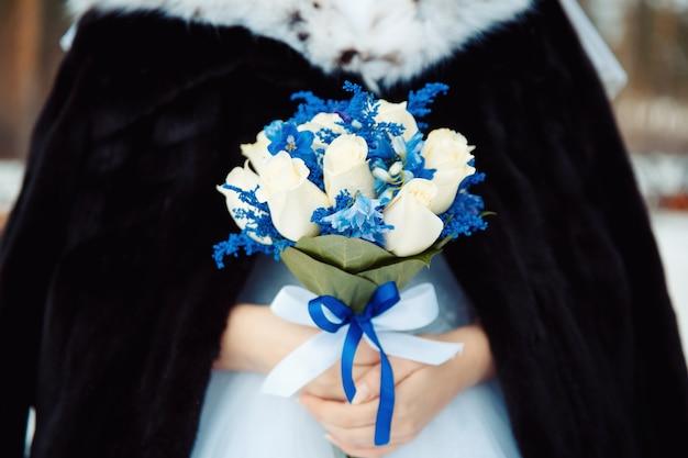 Bruid met boeket verse witte rozen en delphinium in bontjas. creatief winter bruidsboeket
