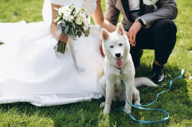 Bruid met bruidegom met hun hond op hun trouwdag