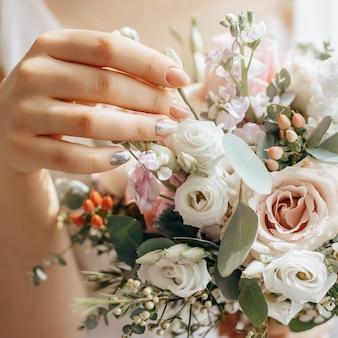 Bruid met bruidsboeket met witte en roze bloemen