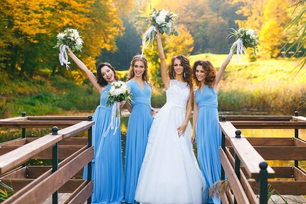 Bruid met bruidsmeisjes in het park op de trouwdag