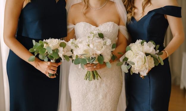 Bruid met bruidsmeisjes staat in jurken met boeketten van pioenrozen